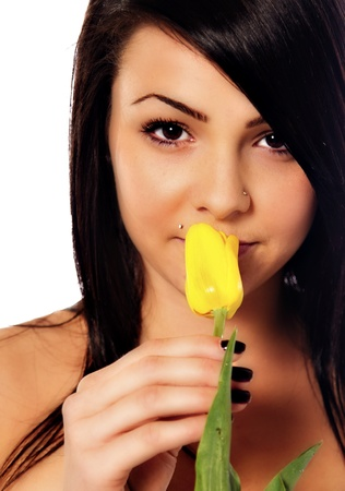 A raven-haired young woman holding a yellow tulip. Stok Fotoğraf