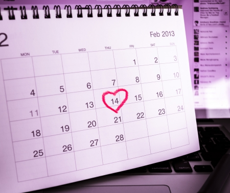 Valentines Day Calendar on notebook computer in real office. Stock Photo