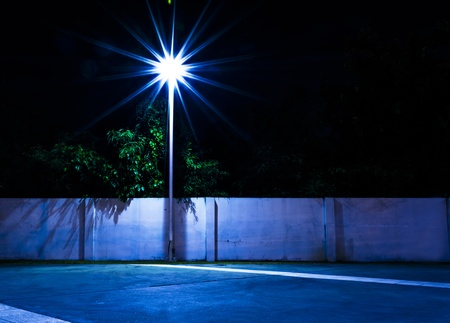 Light and Brick Wall on park at night time. Stock Photo