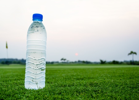 Cold Drinking water bottle on beautiful green field
