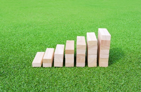 Wood Graph on the green Field for success and achievement concept. Stock Photo