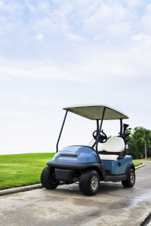 A golf cart with clubs on way to the Golf Course. Stock Photo