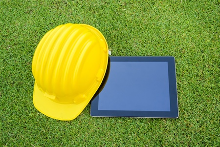 Tablet and Safety helmet on the greenfield. copy space for advertising.