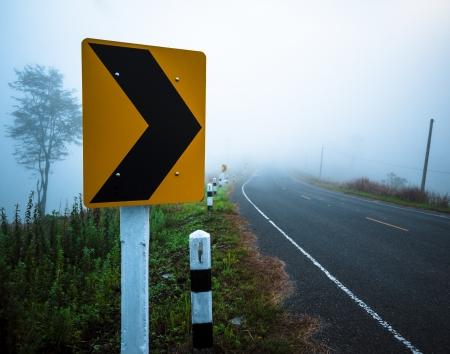 Se�al de tr�fico en un road.Turn Derecho a la niebla de la ma�ana. photo