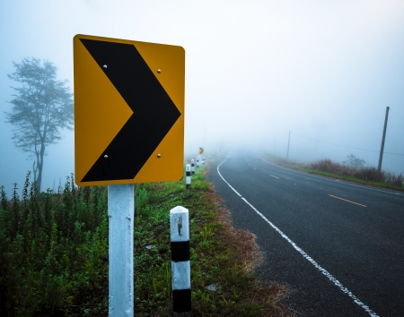 Traffic sign on a road.Turn Right to the mist in the morning.