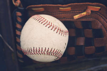 Black and brown baseball glove with ball lyaing on top for game.