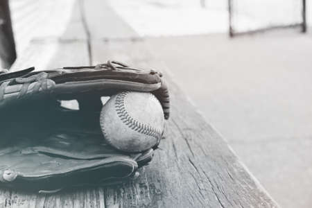 Baseball in glove laying on dugout bench in black and white. Stock Photo