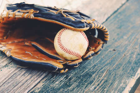 Baseball in game glove on wood dugout bench Stock Photo