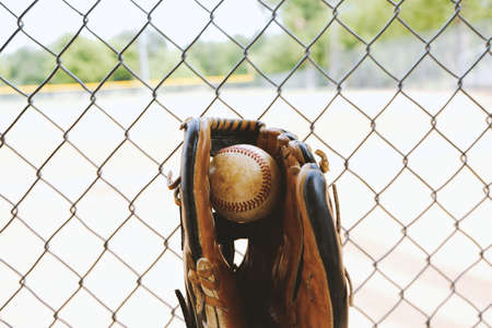 Old used ball in glove, view from team dugout.  Baseball field in background. Stock Photo - 121365572