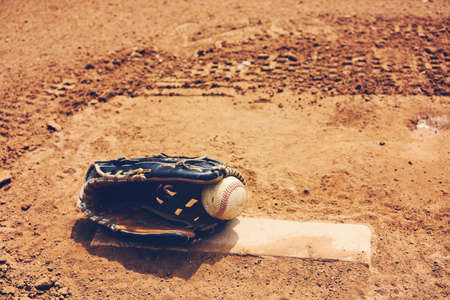 Ball for baseball game in glove on mound with dirt field in background. 免版税图像