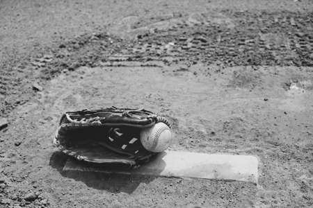 Old baseball lays in players glove on pitchers mound of field for game.