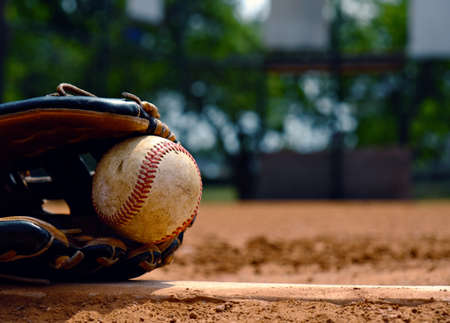 Baseball in glove laying on pitchers mound of ball field.  Old used sports equipment for team sport.
