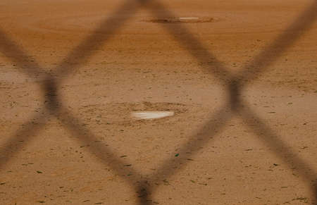 Dirt of baseball field shows game diamond with pitchers mound through dugout fence.
