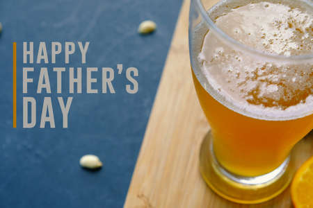 Happy fathers day graphic with pint of beer and snacking peanuts in background.  Text for holiday card or banner on black background. Stock Photo