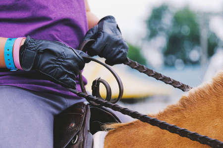 English style rider with leather gloves and reins for horseback riding at show closeup. Stock Photo