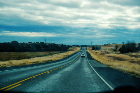 Travel concept with car driving through countryside on road during dreary day.