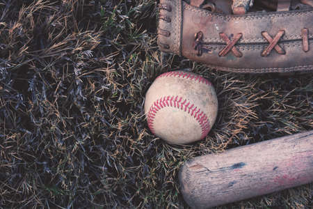 Baseball with bat and glove laying in field grass, grunge style. Stock Photo