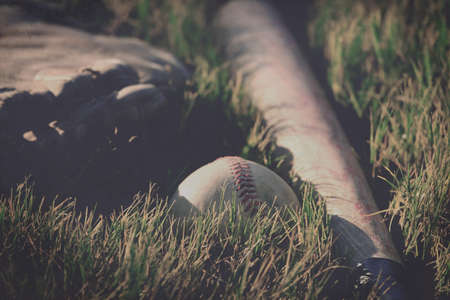 Old baseball in grass with bat and mitt in background for ball season concept. Stock Photo