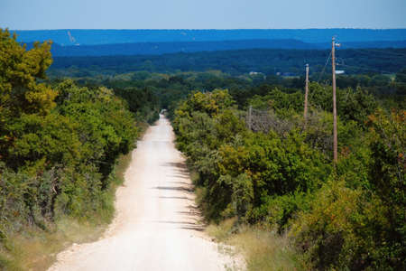 Rural dirt road to horizon in hills of Texas landscape.