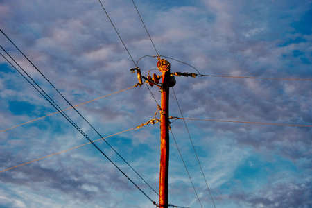 Energy concept with power lines and telephone lines on pole with sky background. Stock Photo