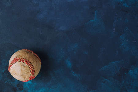 Old used baseball on blue texture background, copy space. 版權商用圖片