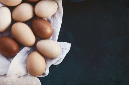 Cage free chicken eggs on towel, copy space on background.
