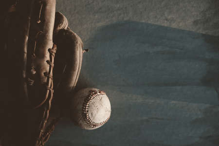 Old used baseball with glove on dark background, copy space for sports concept.