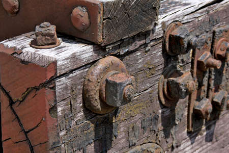 railroad tie: rusted railroad tie with rusty metal nuts and bolts