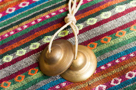 Tibetan bell tingsha on table. Stock Photo