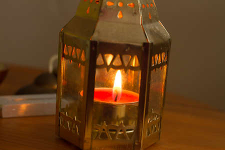pierce: Gold candle on a wood table.