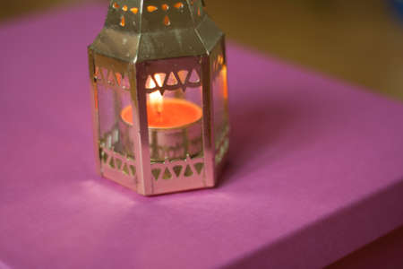 Gold candle on a pink table.