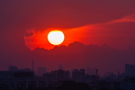 As the sun sets on the horizon are in Bangkok amid tall buildings  photo