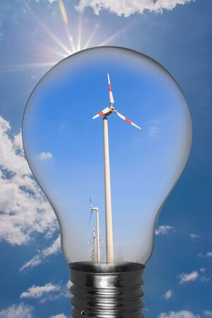Ideas,Wind turbine in light bulb with a sky background with sun  photo