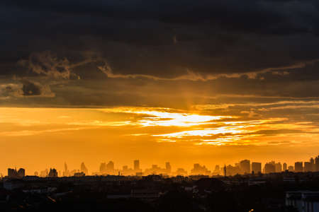 Light of the sunset amidst dark clouds in Bangkok. photo