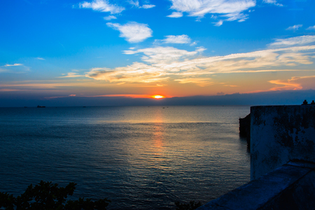 Beautiful sunset sky with clouds on sea photo