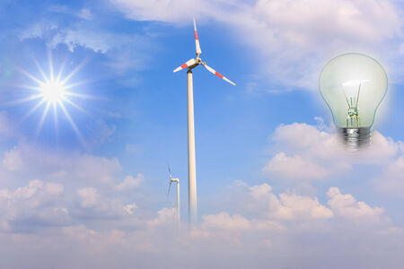 The sun, wind turbines as a source of energy to a light bulb  photo