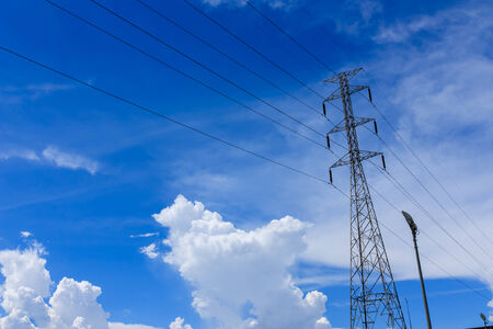 High voltage Pole against blue sky and white clouds  photo