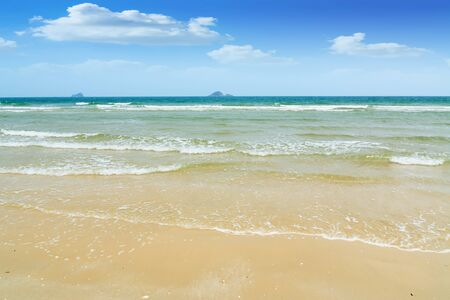 Wave in the sea on the sand beach with blue sky background