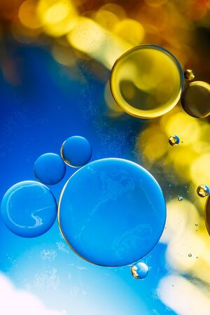 close up oil floating on water with yellow blue background photo