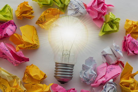 good idea: A good idea is like a light bulb that shines,On white background  and  crumpled colorful paper