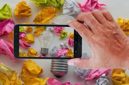 good idea: Smart phones photography a good idea concept with colorful crumpled paper and light bulbs.