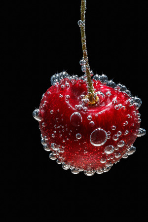cherries isolated: Cherry in water with bubbles, on isolated black background