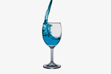 winy: Blue water splash into wine glass isolated on white background.