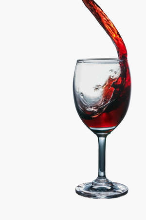 winy: Red wine splash into glass isolated on white background. Stock Photo