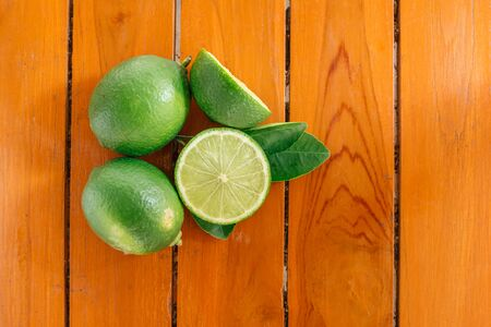 Green lemon with leaves on wood background