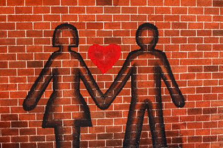 Symbols Men Women shook hands on a red brick wall