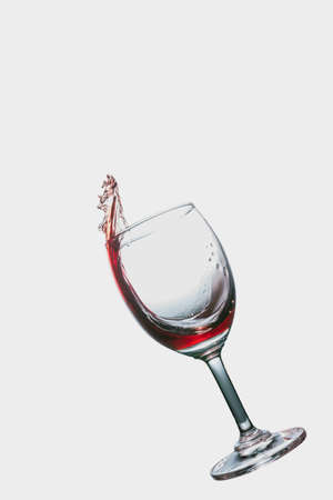 Red wine splash into glass isolated on white background. Stock Photo