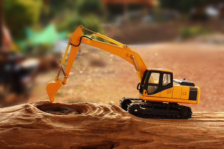 back hoe: Excavator model on wooden with background outdoor