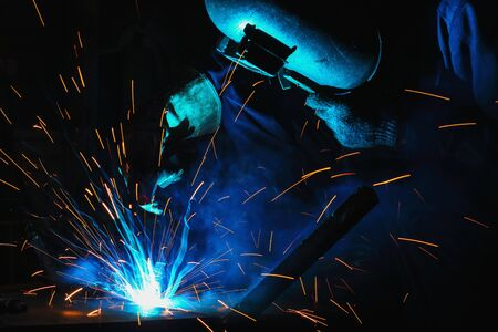 Welder of Metal Welding with sparks and smoke in manufacturing Stock Photo