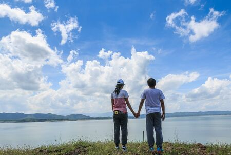 Couples who standing hand in hand looking landscapes.